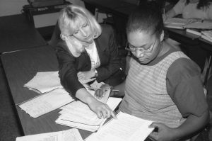 Michele Geers (left), Accounting faculty member, helps unidentified female student with classwork (ca. 1980s)
